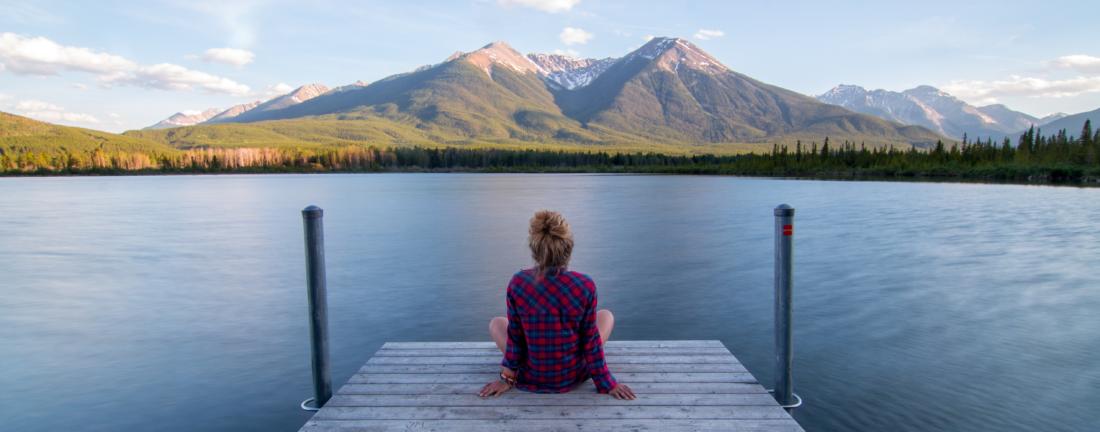 Femme qui regarde un lac et se demande comment trouver une idée de projet professionnel