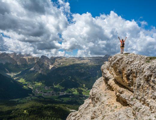 femme bras levés en haut d'une montagne
