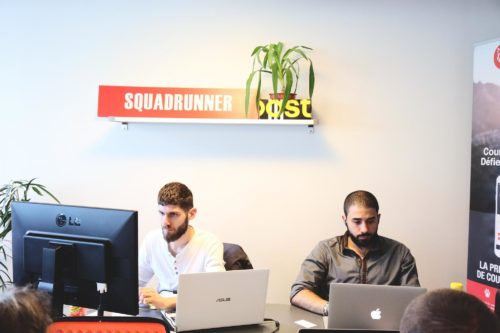 deux hommes assis derrière un ordinateur
