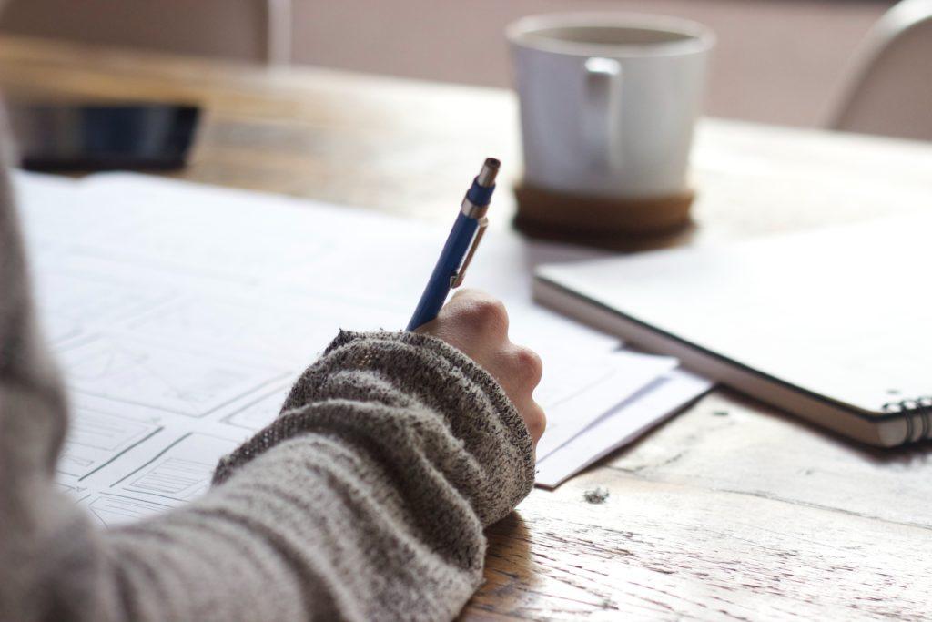 femme écrivant dans un carnet pour lancer son activité sans filet de sécurité