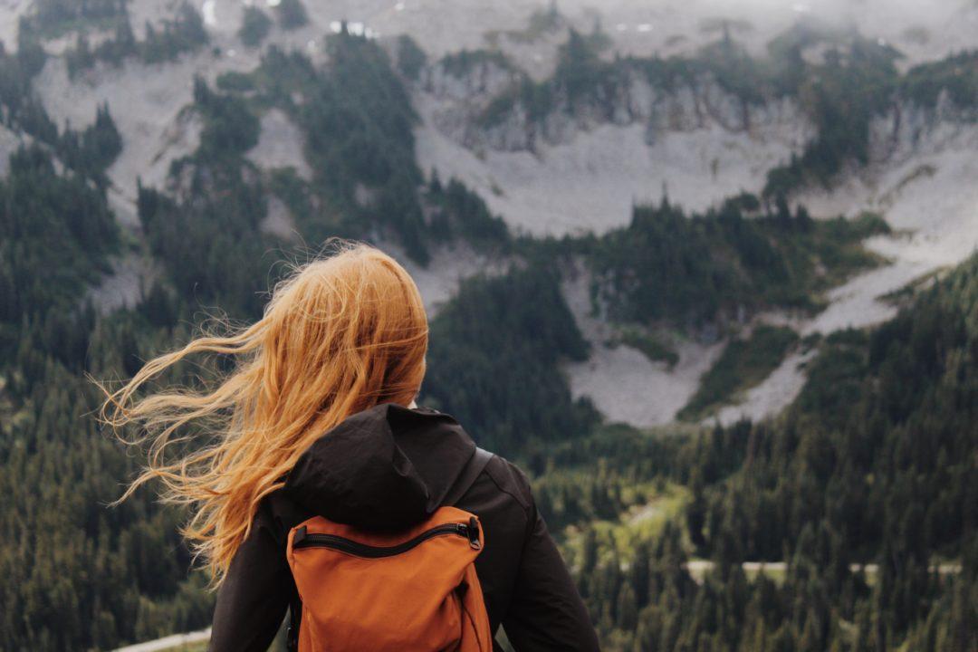 femme blonde regardant l'horizon montagneux