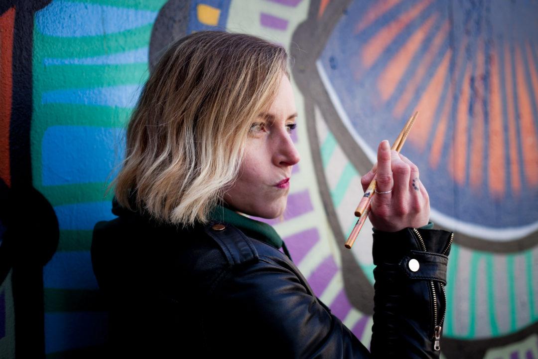 Femme qui tient baguettes pour manger nouilles devant un mur coloré pour illustrer sa reconversion insolite