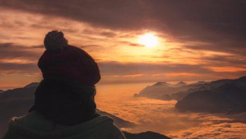 femme sur le haut d'une montagne regarde l'horizon