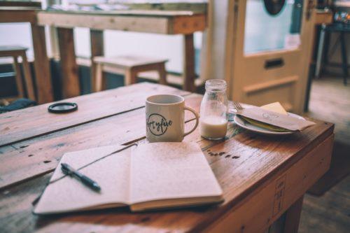 cahier sur une table en bois avec crayon et tasse