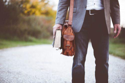 Homme qui marche en tenant un livre et une sacoche