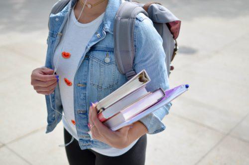 Femme avec livres dans la main qui va reprendre ses études et les financer