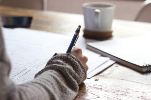 Main qui écrit sur une feuille blanche comment reprendre ses études et les financer