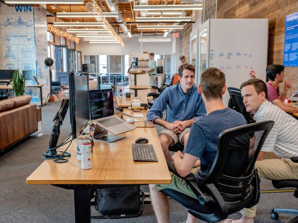 3 personnes discutent pour trouver un développeur