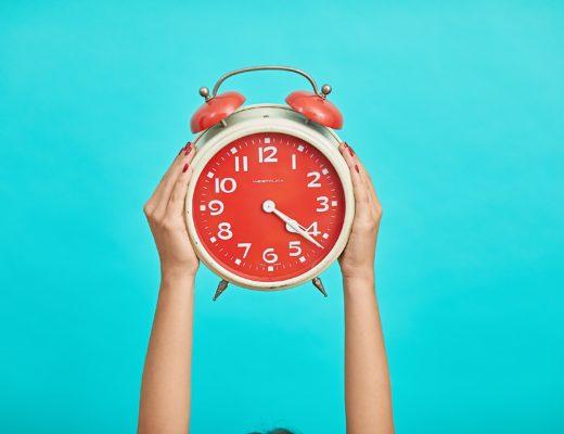 Horloge rouge sur fond bleu qui illustre la procrastination