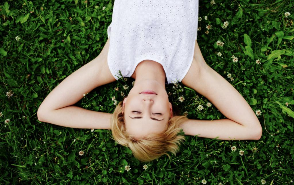 femme allongée sur l'herbe maître Reiki et Sophrologue