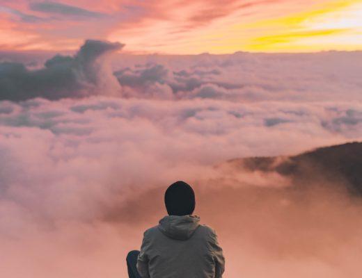 Un homme devant l'horizon assis sur une montagne