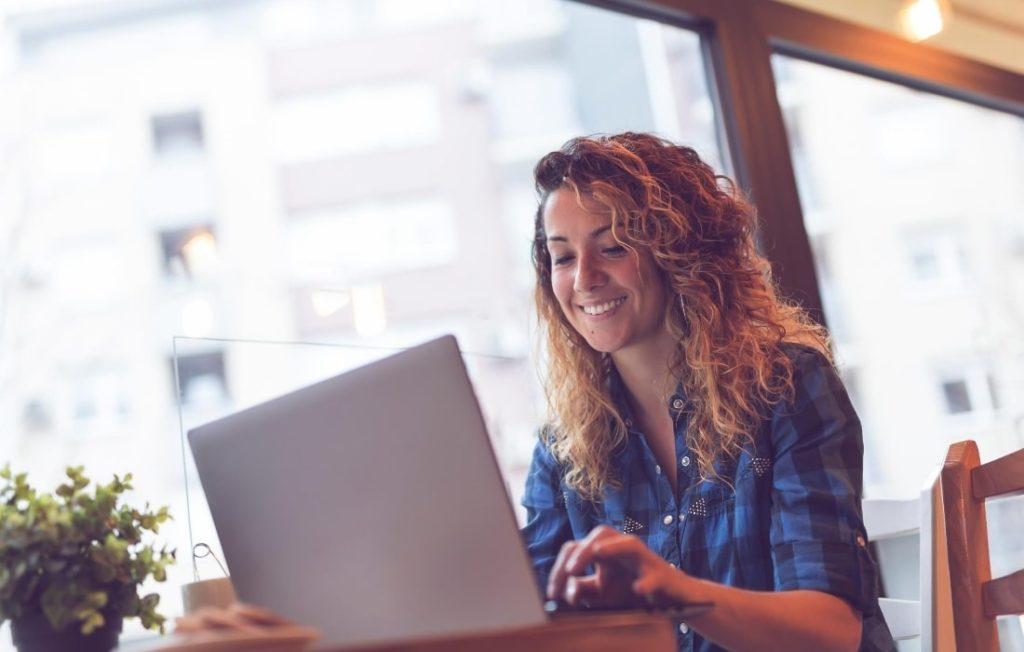 Femme sur son ordinateur qui essaie de fidéliser ses clients en freelance